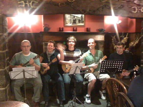 Bangor Uke Club (from left to right - Pete, Jane, Matt, Doug and Simon) preparing to play in the fireplace of the Vaynol Arms in Nant Peris