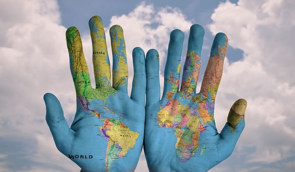 A photo of hand with the world painted on them